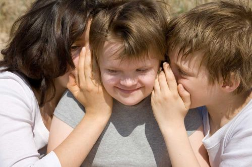 © philidor / Fotolia.com Girl and boy whispering secret to their sister.